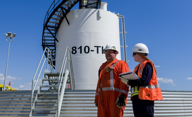 Two workers in front of a crude storage tank